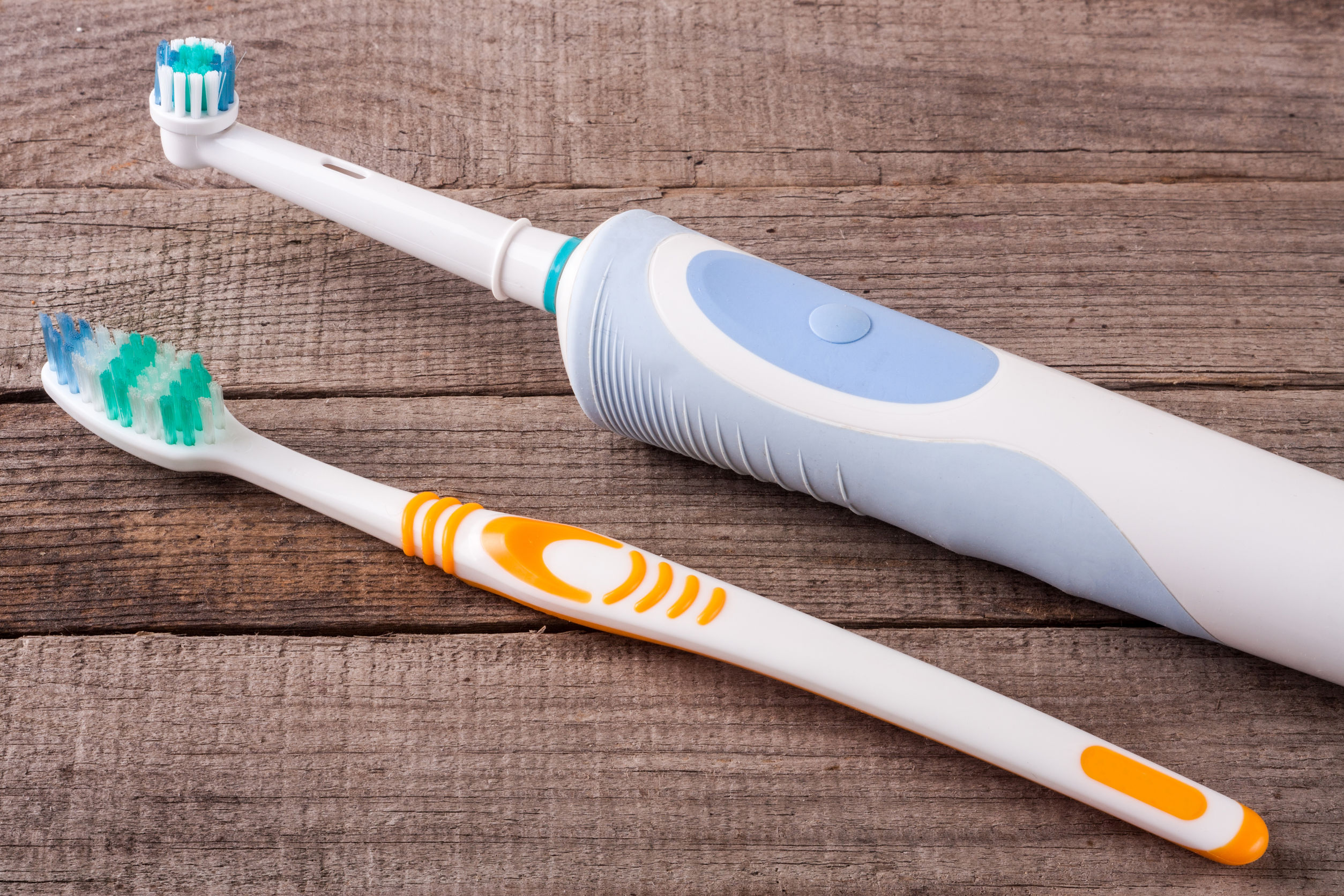 68850378 - electric and manual toothbrushes on the wooden background
