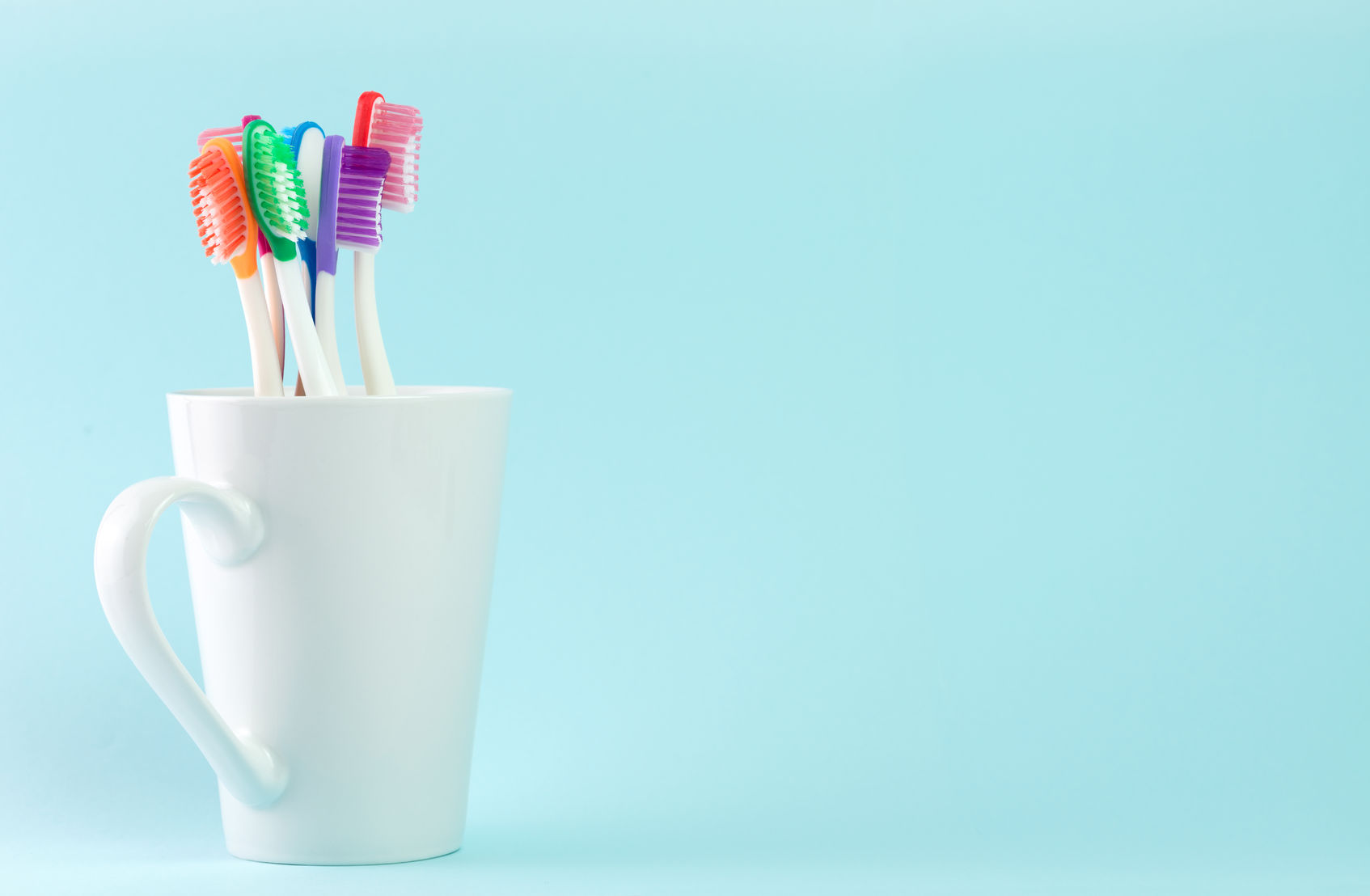 46444107 - multicolor toothbrushes in white mug, with copyspace
