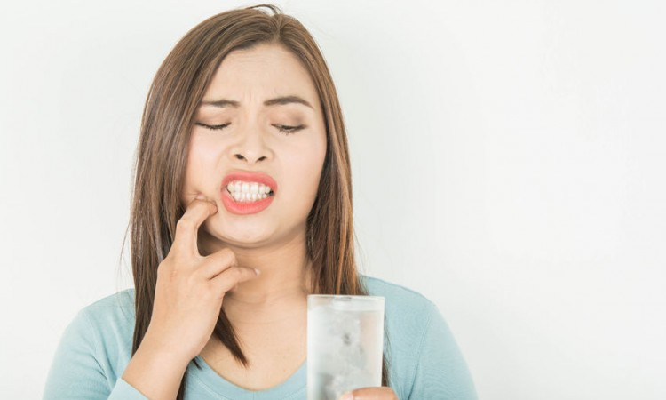 102334261 - sensitive teeth in woman and a glass of cold water.